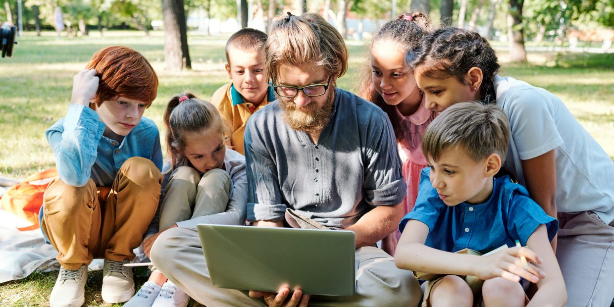 Showing pictures to kids at outdoor class